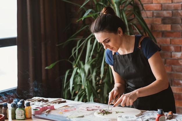 アーティストスタジオ。進行中の粘土の手工芸品。職場でモデリングツールを持つ若い女性。お香の煙。