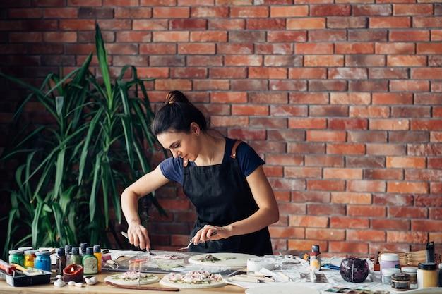 アーティストスタジオ。進行中の粘土の手工芸品。職場でさまざまなモデリングツールを持つ若い女性