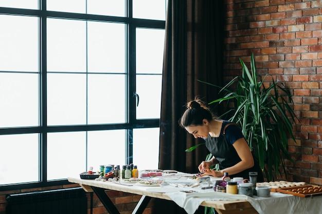 アーティストスタジオ。進行中の手工芸品のアートワーク。職場でモデリングツールを持つ若い女性。