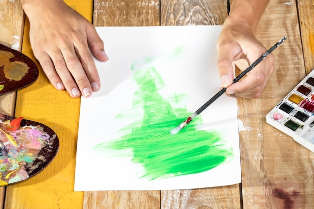 Artist in studio painting with brush