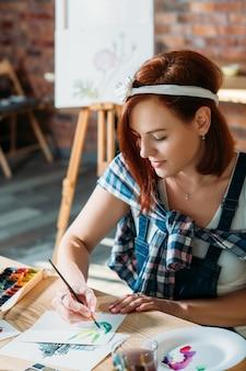 アーティストスタジオ。水彩画の作成。インスピレーションを得てスケッチブラシストロークをしている赤毛の女性。