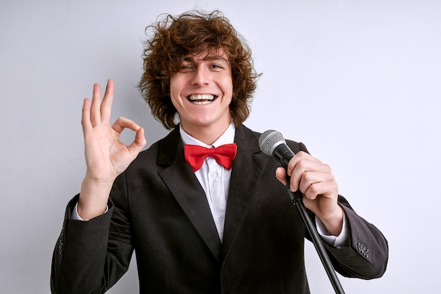 Artist in suit with microphone showing ok gesture and smiling, the presentation or speech is good, successful performance