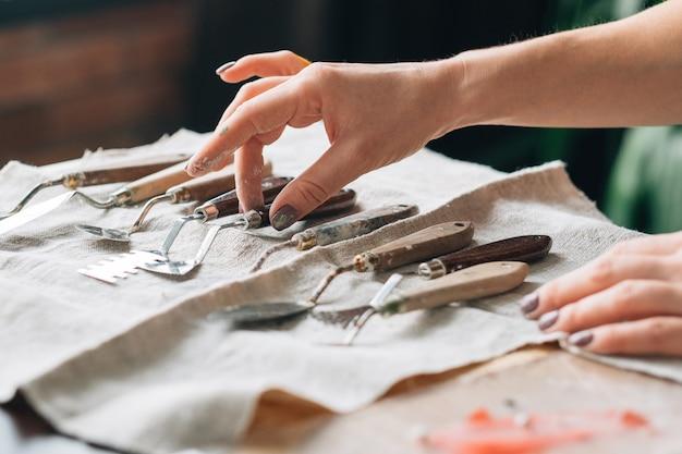 アーティスト用品。アイボリーテキスタイルにアレンジされたアートクラフトセット構成。ツールを選択する女性の手。
