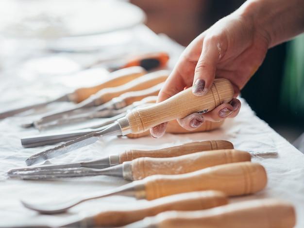 アーティスト用品。テーブルの上に配置されたアートクラフトセットの構成。チゼルツールを選択する女性の手。