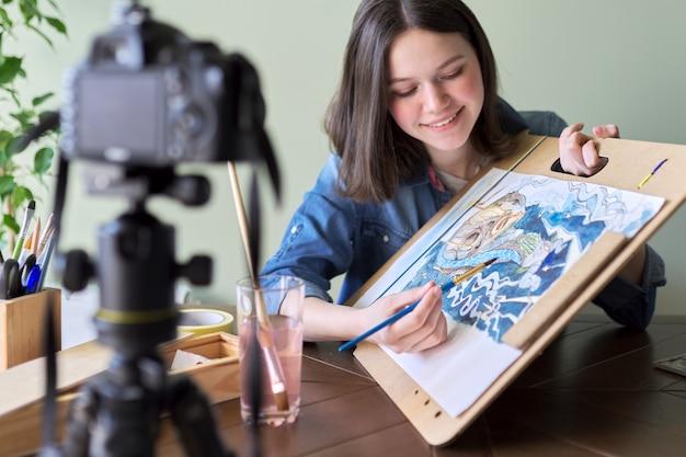 アーティスト、10代の少女は、ブログのビデオカメラに記録を描きます。絵の具、家の絵、三脚のカメラ、ブロガーのvlogerの絵を描いて伝えます。テクノロジー、アート、若者、コミュニケーション、教育の概念