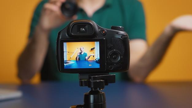 아티스트는 스튜디오에서 vlog 에피소드를 녹화하는 동안 카메라 렌즈를 테스트합니다. 카메라 렌즈 기술 디지털 녹화 소셜 미디어 인플루언서 콘텐츠 제작자, 팟캐스트, 브이로그, 블로그 전문 스튜디오
