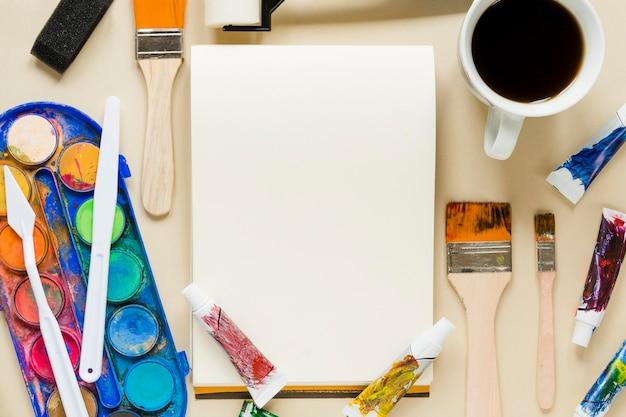 Collezione di strumenti dell'artista con una tazza di caffè