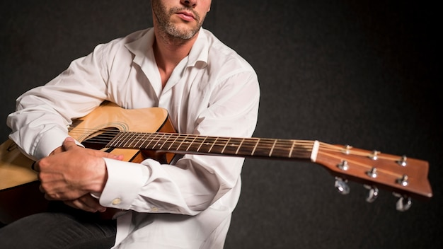 Artist in white shirt holding his acoustic guitar