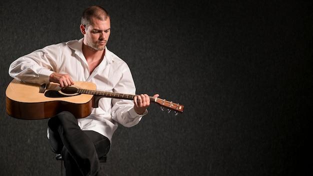Artista in camicia bianca che gioca lo spazio della copia della chitarra