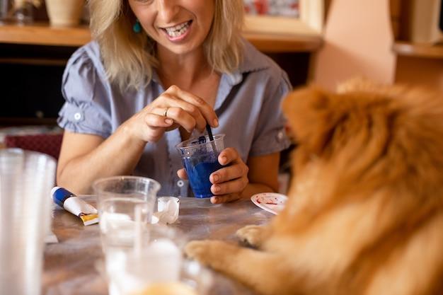 カップに青い絵の具を混ぜるアーティストは、気配りのある補助犬を飼っています。趣味と創造性。在宅勤務。インスピレーションと自由。幸福と相互理解。