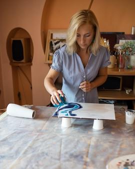 Художница с помощью красок создает современный интерьерный рисунок, работает в своей мастерской. счастья и творчества. дизайн интерьера. домашний отдых. мастер класс.