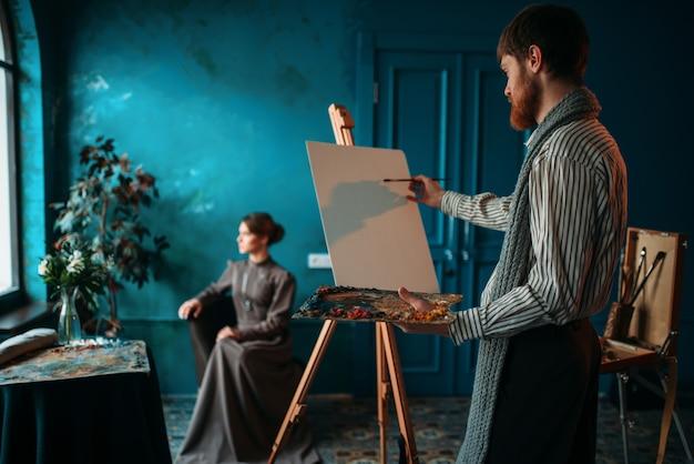 イーゼルの前にパレットとブラシを持つアーティスト