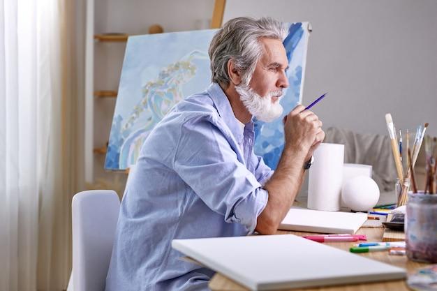밝은 방에서 연필로 예술가는 생각에 묵상에 앉아 있습니다. 집에서. 예술, 공예, 상상력 개념. 측면보기