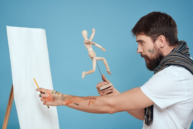 Artist with a wooden dummy in hands drawing