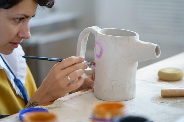アーティストの女性は、陶器スタジオの陶芸家の職場で粘土の水差しに飾りを作成する絵筆を保持します