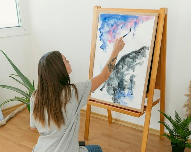 後ろからキャンバスに絵を描くアーティストの女性