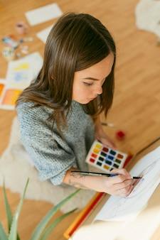 キャンバスの高いビューに絵を描くアーティストの女性