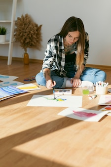 床に絵を描くアーティストの女性