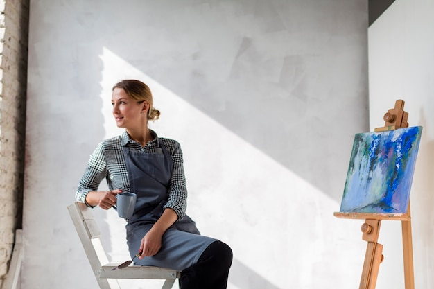 Artist woman posing on chair with canvas