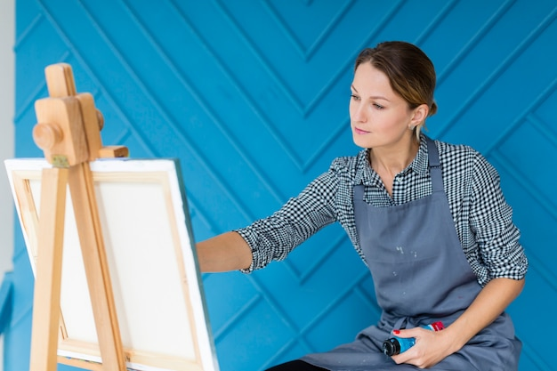 Artist working on painting in apron