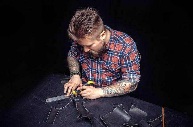 Художник, работающий с кожей, создает в магазине качественные изделия из кожи.