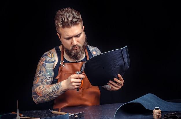 Художник, работающий с кожей, вырезает контуры кожи для своей новой работы в кожевенной студии.