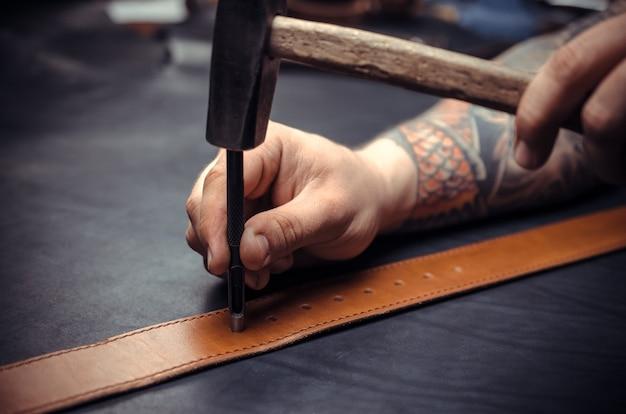 Художник, работающий с кожей, вырезает контуры кожи для своей новой работы