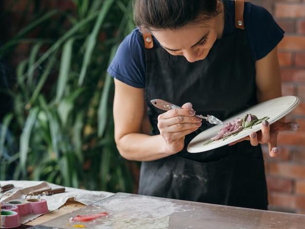 アーティストの職場。インスピレーション。進行中のセラミックアートワーク。スタジオで作業するモデリングツールを持つエプロンの女性。