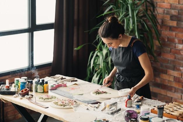 アーティストの職場。インスピレーション。進行中のセラミックアートワーク。スタジオで働くモデリングツールを持つ女性。
