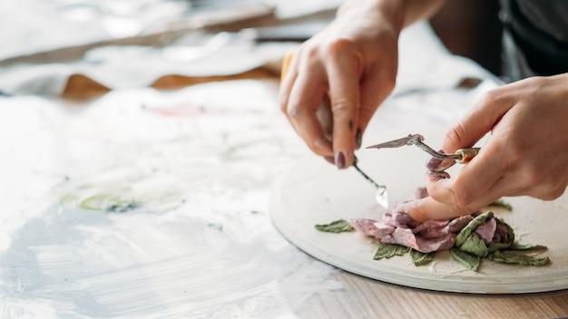 アーティストの職場。インスピレーション。セラミックの花のアートワークが進行中です。スタジオで働くモデリングツールを持つ女性。