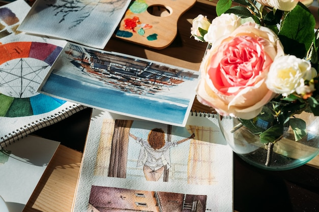 Artist workplace. painter studio atmosphere. watercolor artworks and flowers with art supplies around.