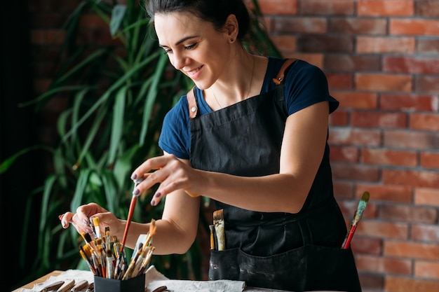 アーティストの職場。スタジオの雰囲気。進行中のアートワーク。絵筆を選ぶエプロンで笑顔の若い女性。