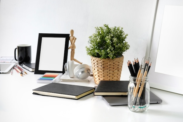 Artist workplace table with pencil, sketch book, photo frame and plant decoration.