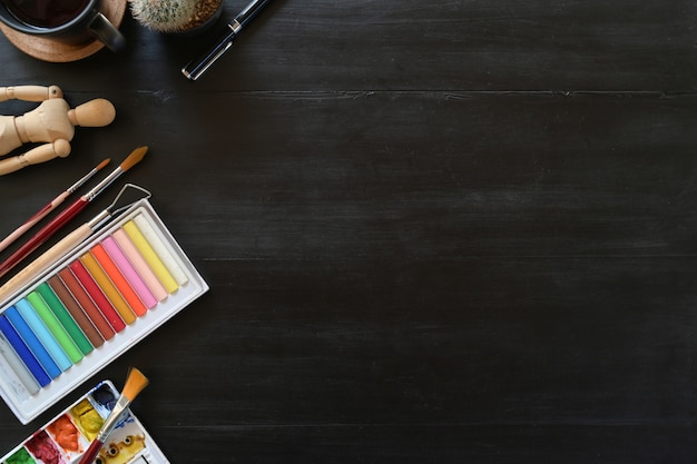 Artist workspace colour with creative accessories on dark wood table. workspace and copy space.