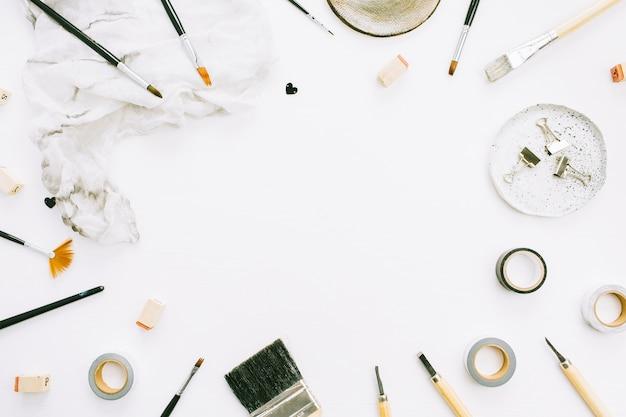 白い背景にペイント ブラシとツールのアーティスト ワークスペース フレーム。テキスト用のスペースを持つクリエイティブなブログ テンプレート。平置き
