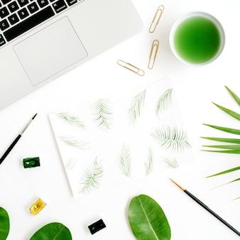 アーティストワークスペース。水彩、ペイントブラシ、ラップトップ、緑のヤシの葉で描かれたヤシの葉