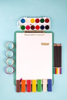 Artist workspace with colorful painting stuff and paper sheets on a pastel blue background. flat lay