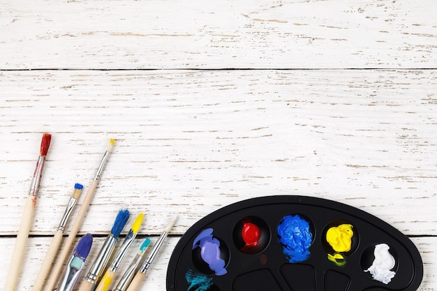 Художественные аксессуары палитра с красками и кистями для рисования на деревянном столе с местом для текста.