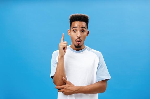 Художественный и креативный темнокожий парень в модной футболке, складывая губы в вау, поднимая указательный палец в жесте эврики, создавая отличную идею, добавляя предложение, как решить ситуацию над синей стеной
