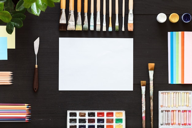 Artistic background concept, creative supplies, paints and paper on black desk