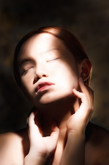 Artistic beauty portrait of young woman with creative lighting effect.