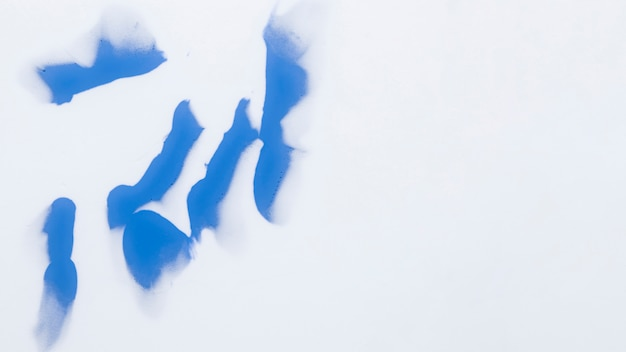 Artistic blue paint strokes isolated over white surface