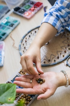 Artistic female hands use colorful beads for creating native tribal indian amulet dreamcatcher