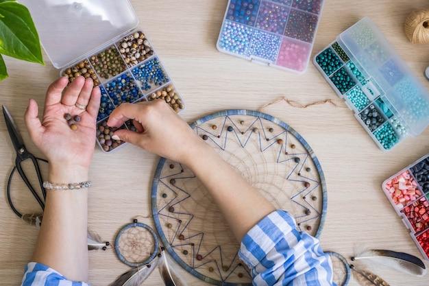 芸術的な女性の手は、ネイティブの部族のインドのお守りドリームキャッチャーを作成するためにカラフルなビーズを使用しています