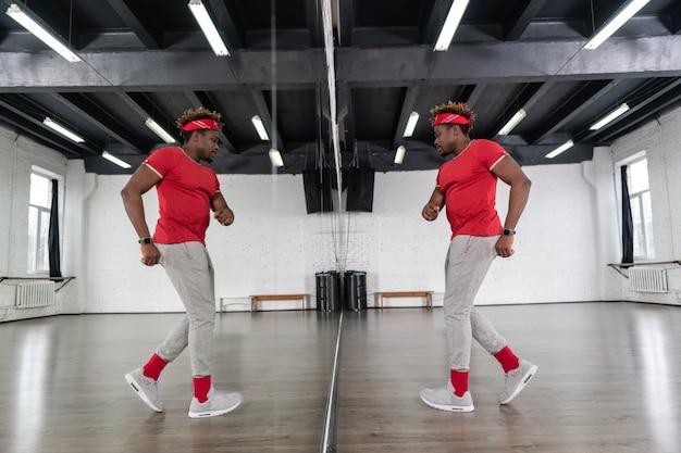 鏡の中の動きを調べながら、モダンなスタイルのダンスに集中している芸術的な格好良い男