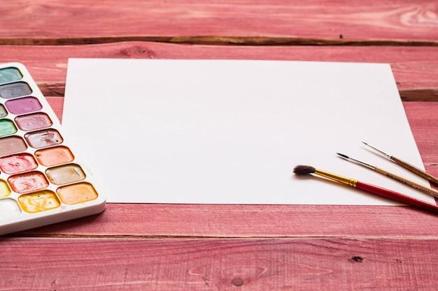 Художественный макет с пустым белым листом бумаги и художественными принадлежностями, включая акварель
