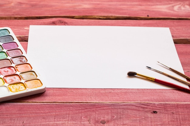 Artistic mockup with empty white sheet of paper and art supplies around including watercolor