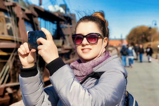 예술적 노이즈 필름 그레인. 전화, 스탠드 및 상트페테르부르크 명소의 사진을 찍는 세로 젊은 관광 여자. 놀라운 여행과 잊을 수 없는 모험의 개념. 복사 공간