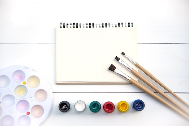 Artistic paintbrushes, placed on a drawing book with watercolors.
