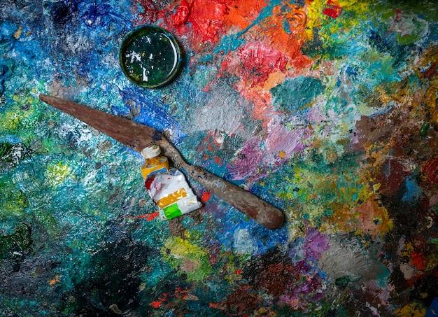 古い木製パレットの芸術的なパレットナイフとペンキのチューブ